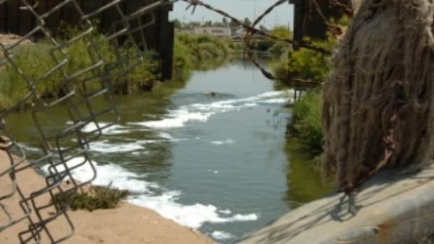 The open sewer New River runs past many low-income homes in Calexico, California.