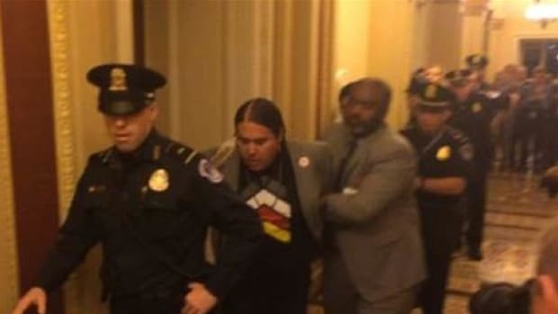 Greg Grey Cloud being led away from Senate chambers by police after bursting into a Lakota song following the narrow defeat of legislation that would have enabled construction of the controversial Keystone XL oil pipeline.