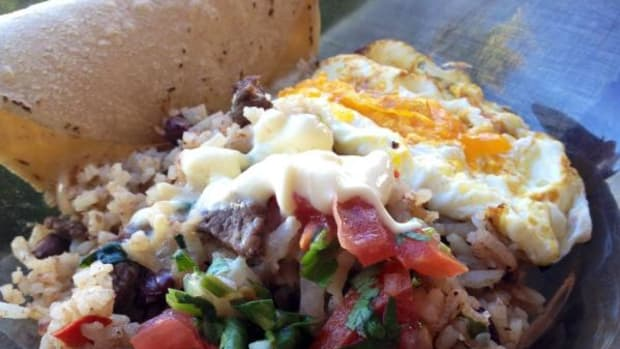 A typical Costa Rican breakfast: Gallo pinto served with fresh tomatoes and a dollop of sour cream alongside a tortilla and a fried egg