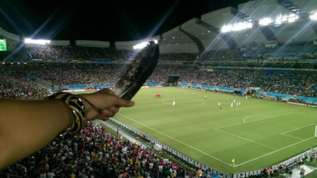 Temyrss Lane holds out her Golden Eagle Feather in Natal, Brazil during the USA vs. Ghana game at the World Cup on June 16, 2014.