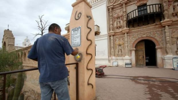 Ivan Burrell, a maintenance worker and janitor, removes the graffiti in front of the San Xavier del Bac Mission located on the San Xavier District of the Tohono O'odham Nation, April 7, 2016.