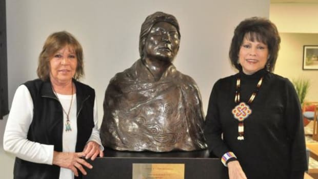 (L to R) Cherokee artist Jane Osti and Cherokee Nation Tribal Councilor Victoria Vazquez stand next to the bronze bust of the late Cherokee National Treasure Anna Belle Sixkiller Mitchell. Courtesy Cherokee Nation.