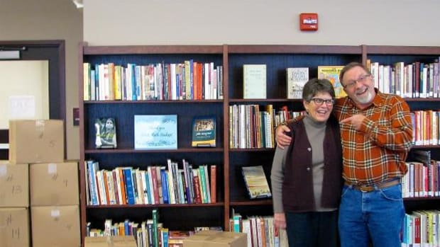 """Ruth and Leo Soukup posing with the 700 books they donated to Red Lake Tribal College discuss who """"snagged"""" who when they met at Ponemah in 1979 as teachers."""