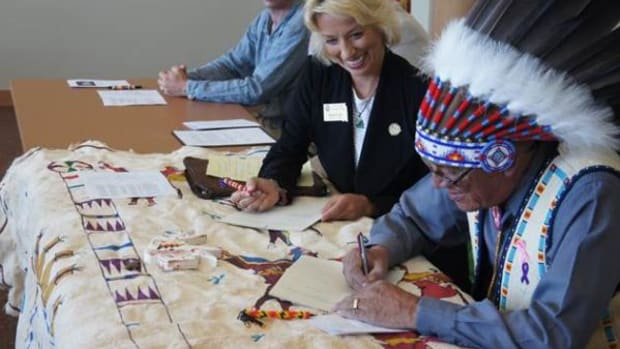 In a bid to increase economic development on Pine Ridge, Oglala Sioux Tribe President John Yellowbird Steele (right) and South Dakota Secretary of State Shantel Krebs sign a Memorandum of Understanding that renews the tribe's access to the state's central filing system for secured loans.
