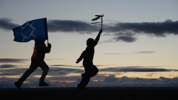 Youth carrying the Cheyenne flag at a past Fort Robinson Outbreak Spiritual Run. This year's run will end at a Busby, Montana gravesite of Cheyenne ancestors whose remains were repatriated from a U.S. Army facility. (Photo courtesy Conscious Alliance)