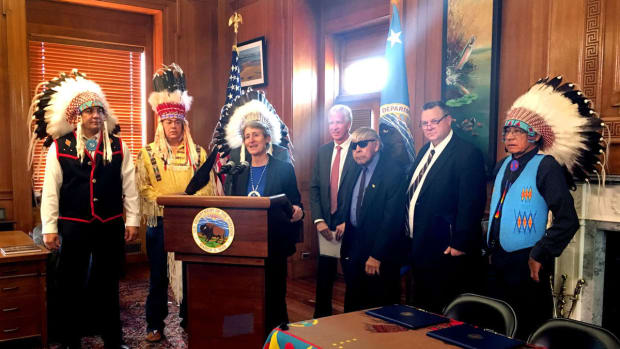 Accompanied by five Blackfeet tribal leaders, David Hager, president of Devon Energy, and Sen. Jon Tester, Interior Secretary Sally Jewell announces the cancellation of 15 energy exploration leases in the Badger-Two Medicine area on Wednesday, November 16. Blackfeet tribal leaders attending the signing of the cancellation in Washington DC are, from left, Tyson Running Wolf, Tim Davis, Harry Barnes (hidden behind Jewell), Earl Old Person (in sunglasses) and John Murray.