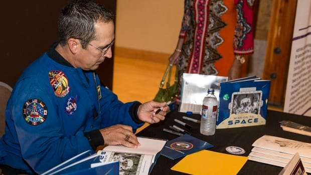 """John Herrington signs a copy of his children's book """"Mission to Space"""" at the 2016 Chickasaw Cultural Evening."""