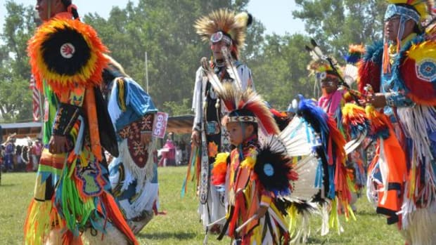 "Dancers in regalia take to the pow wow grounds at the Oglala Nation Pow Wow in 2014. Dictionary.com officially defines a powwow as an event where Native Americans practice ""magic."""