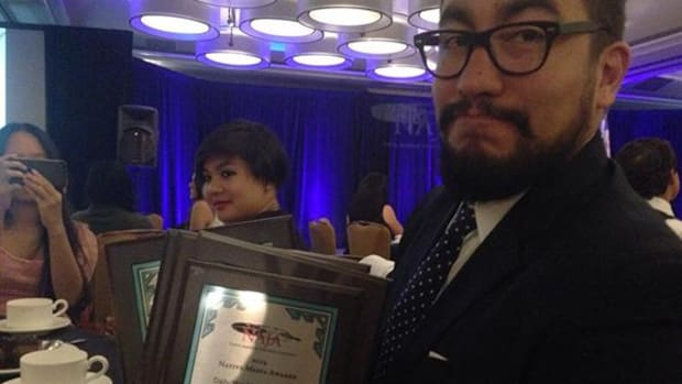 Tristan Ahtone holding the five plaques he won at the 2014 National Native Media Conference. Photo by Katherine Lanpher.