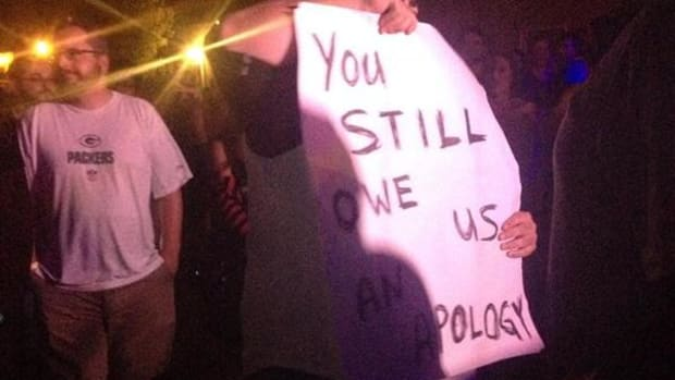 Journalist and protester Louis Fowler holds a sign at Pink Pony's controversial Norman Music Festival performance.