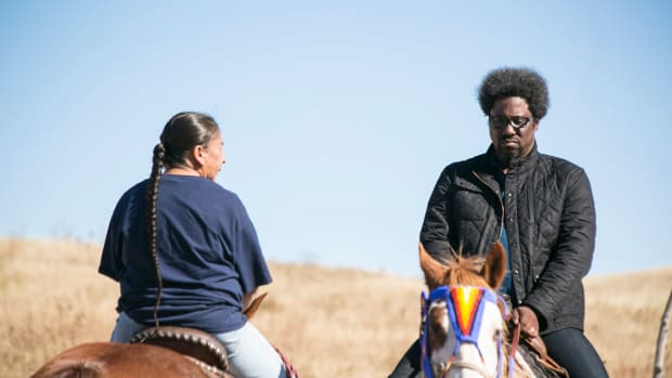 W. Kamau Bell, right, comedian and host of 'United Shades of America,' rides a horse with Victoria Hawk, Lakota Animal Caregiver.