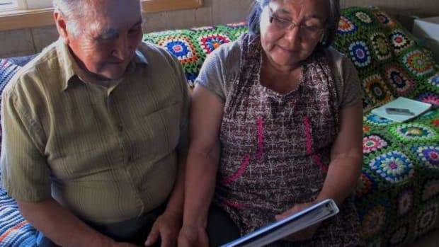 At their home in Manokotak, Alaska, Mike and Anecia Toyukak page through a notebook of elementary-school mathematics lessons based on traditional Yup'ik concepts. They are part of a team that has created the curriculum.