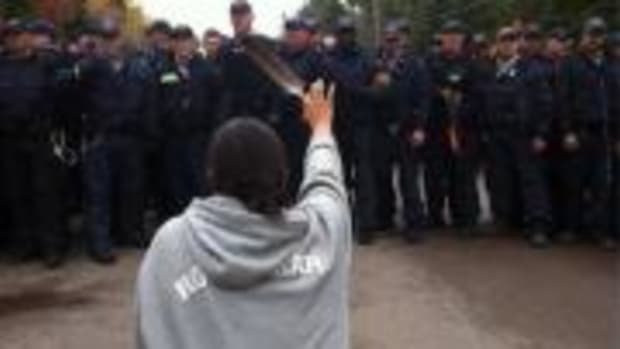 This photo of 28-year-old Amanda Polchies kneeling before Royal Canadian Mounted Police while brandishing an eagle feather during anti-fracking protests in New Brunswick has become iconic as a symbol of resistance to destructive industrial development—and of women's role in fighting for the water.