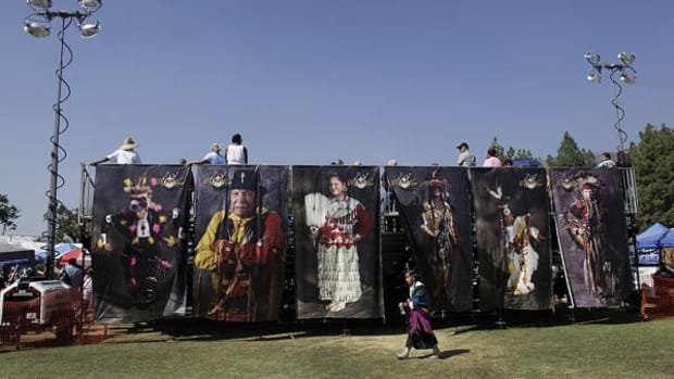 A young fancy shawl dancer walks by hung photographic murals of powwow dancers from previous years, during the San Manuel Band of Mission Indians' Annual Pow Wow.