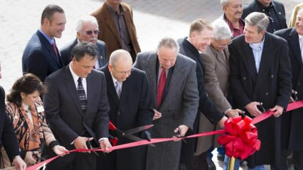 Chickasaw Nation Governor Bill Anoatubby, center with large scissors, is joined  by tribal and local officials and distinguished guests Nov. 14 during a ribbon-cutting ceremony in Sulphur, Okla., to open a trio of new attractions in Chickasaw Country; the Chickasaw Visitor Center, ARTesian Gallery and Studios and Bedre Café.
