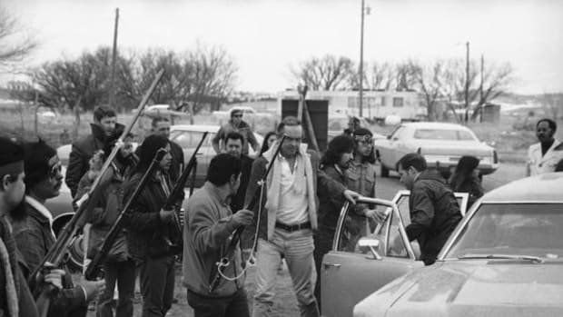 Harlington Wood, right, of the U.S. Attorney General's office, is escorted by armed AIM supporters from car to conference with AIM leaders in Wounded Knee, South Dakota, March 19, 1973, as efforts to end the occupation of Wounded Knee continue.