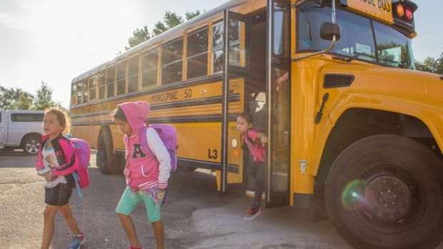 Students hop off the brand new school bus on the first day of school at Red Cloud.