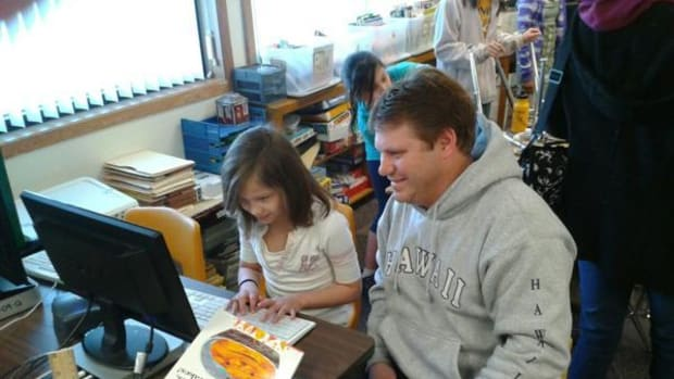 A third-grader in the Mahnomen Public School District shows dad her reading program.
