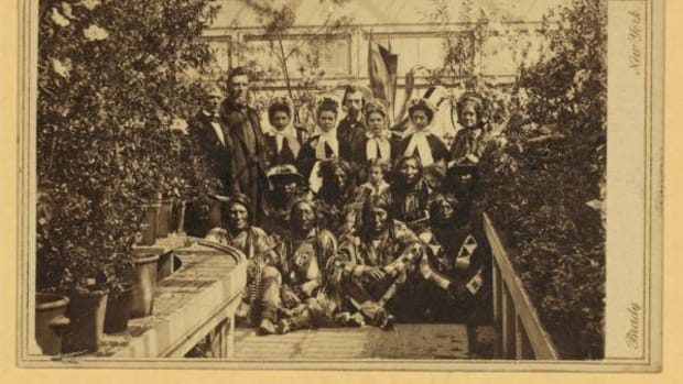 This image shows the Southern Plains Indian delegation in the White House Conservatory on March 27, 1863 during the Civil War. The interpreter William Simpson Smith and the agent Samuel G. Colley are standing at the left of the group; the white woman standing at the far right is often identified as Mary Todd Lincoln. The Indians in the front row are, from left: War Bonnet, Standing in the Water, and Lean Bear of the Cheyennes, and Yellow Wolf of the Kiowas. Yellow Wolf is wearing the Thomas Jefferson peace medal that aroused such interest. The identities of the Indians of the second row are unknown. Within 18 months from the date of this sitting, all four men in the front row were dead. Yellow Wolf died of pneumonia a few days after the picture was taken; War Bonnet and Standing in the Water died in the Sand Creek Massacre; and Lean Bear was killed by troops from Colorado Territory who mistook him for a hostile.
