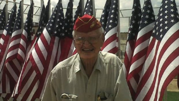 The late Navajo Code Talker Wilfred E. Billey stands proudly before American flags.