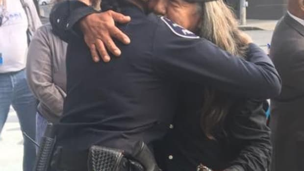 """Rick Williams, older brother of Seattle police shooting victim John T. Williams, hugs Detective Denise """"Cookie"""" Bouldin at the ground-breaking ceremony for the White Deer Crossing Community Crosswalk on September 11. This is the first gesture of forgiveness toward Seattle police Rick has made since the death of his brother six years ago."""