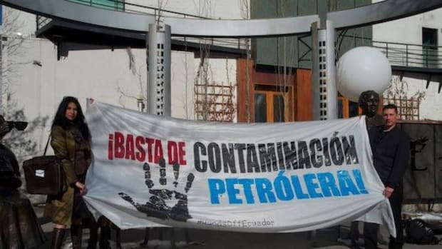 Actress Michelle Thrush, left, poses with a banner decrying oil development in the Amazon region of Ecuador.