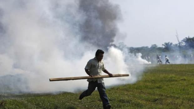 A man runs for cover after riot police fired a tear gas canister during a protest in Rurrenabaque, Bolivia, today. Bolivia's Defense Minister Cecilia Chacon resigned Monday after police violently broke up a Sunday protest by indigenous and environmentalists groups who were marching towards La Paz, against the construction of a government planned highway that would cut through the nature preserve Territorio Indigena Parque Nacional Isiboro Secure, TIPNIS, home to 15,000 natives.