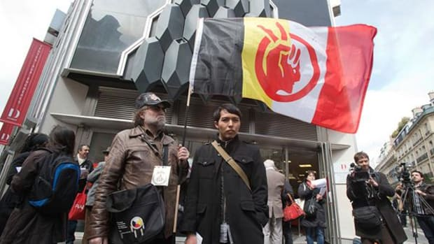 A French supporter of the Indian cause, who refused to give his name, left, holds a flag of the American Indian Movement and an American exchange student, member of the Arizona's Hopi tribe, Bo Lomahquahu, right, stand outside of the Druout's auction house to protest the auction of Native American Hopi tribe masks in Paris, Friday, April 12, 2013.