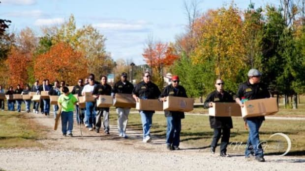 File-The Saginaw Chippewa Indian Tribe Men's Society walks to the Nibokaan Ancestral Cemetery in Mt. Pleasant, Michigan, on October 12, 2012. They are carrying remains returned with the help of NAGPRA.