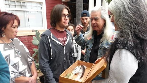 Grey Wolf (Walter Ruiz) and Corine Fairbanks of AIM give eagle feathers to Caroline Ward and son, Kagen at the Los Angeles Worker Center.