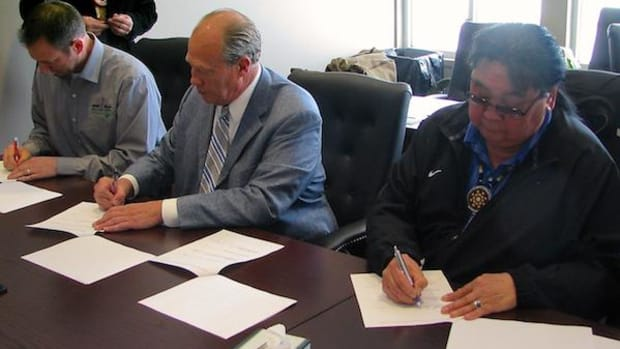 Left to right: David Winkelman of Innovative Power Systems, Robert Olson, president of Olson Energy, and Red Lake Band of Chippewa Chairman Band Chairman Darrell G. Seki Sr. ink the deal to bring the Nation solar.