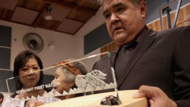 Anietsachist, Victor Amos of the Hesquiaht First Nation (right), accepts a gift from BC Aboriginal Affairs Minister Ida Chong (far left), at a feast on November 16. Chong expressed regret on behalf of the BC government for the wrongful hanging of two Hesquiaht men in 1869. (Photo: Wawmeesh Hamilton)
