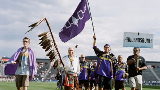 Oren Lyons stands amidst the Iroquois Nationals with an eagle staff in Spirit Game: Pride of a Nation. Courtesy One Bowl Productions