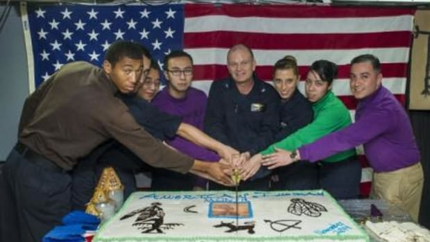 Capt. Greg Fenton, commanding officer of the Nimitz-class aircraft carrier USS George Washington (CVN 73), center, performs a cake-cutting ceremony with members of the crew during an American Indian Heritage Month celebration on the ship's mess decks.