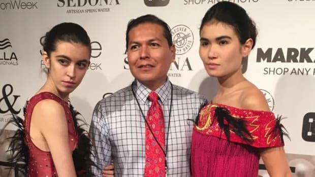 Navajo fashion designer Orlando Dugi is seen after his show with two of the models who walked in his designs.