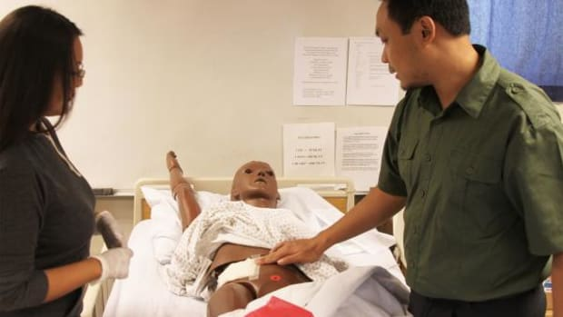 """NTU nursing instructor Jonathan Lumibao assists a student while practicing classroom techniques on a dummy. """"Simulations are getting popular in the nursing field these days,"""" explained Lumibao. """"It gives students scenarios and lets them practice in a controlled environment."""" Lumibao received a Master's of Science degree in Nursing Education from the University of New Mexico on December 11, 2014."""
