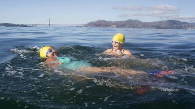 Elizabeth Best (Colville Confederated Tribes) gets encouragement from South End Rowing Club (San Francisco) support swimmer Tina Voight as they swim from Alcatraz Island to San Francisco on October 19, 2015.