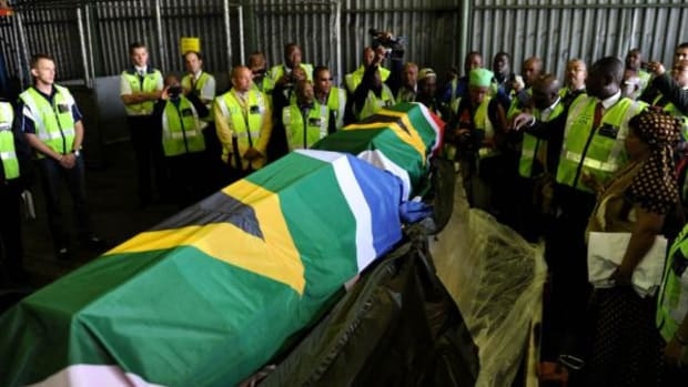 Government officials, media and relatives surround the coffins, draped in South African flags, as the remains of Khoisan couple Klaas and Trooi Pienaar are returned from Austria, at OR Tambo International Airport in Johannesburg Friday, April 20. 2012.  In 1909, their bodies were exhumed by Austrian anthropologist Rudolf Poch, who claimed to be doing research on dwarfism.