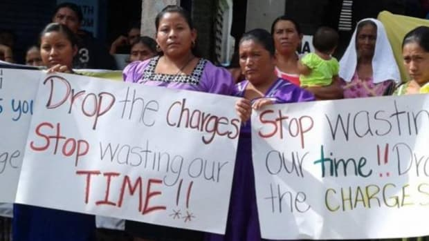 Supporters of the 13 Mayan villagers and leaders arrested by Belizean police last year hold signs waiting for their release.