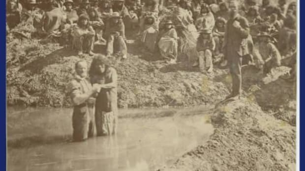Daniel D. MacArthur is seen here baptizing Paiute Indians in a stream near St. George, Utah. Augustus P. Hardy is shown standing on the bank.