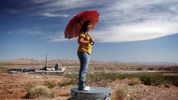 Moapa Paiute Vickie Simmons, in the film An Ill Wind, holds a virtually useless umbrella to protect her from coal power plant dust storms that make her heart race.
