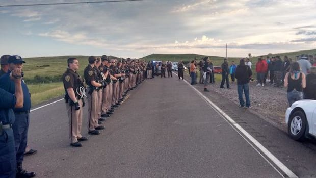 Police line up before protesters near the construction site of the Dakota Access oil pipeline.