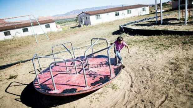 Using decades-old playground equipment, a student plays on a merry-go-round at Cove Day School in Red Valley, Arizona—a BIE school. Abandoned uranium mines that once brought an employment boom to the area are scattered throughout the hills in the background. At least 19 tribal schools in Arizona went four years or more without the inspections that are supposed to be performed yearly by the BIA.