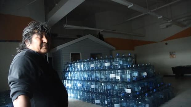 Shoal Lake 40 First Nation drug and alcohol counsellor Stewart Redsky stands surrounded by the band's drinking water jugs, stacked in what used to be the community's youth center until their water storage shed's floor collapsed.