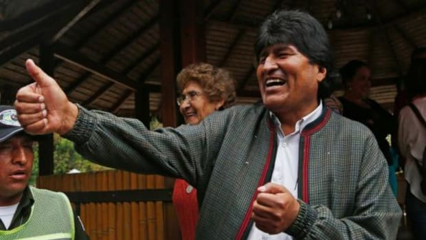 Bolivia's President Evo Morales gives a thumbs up to people at a trout farm where he stopped to eat in Paracti, Bolivia, Saturday, Oct. 11, 2014. Morales stopped here to eat as he traveled to the city where he'll vote in tomorrow's general election. Morales is running for a third term in Sunday's presidential elections.