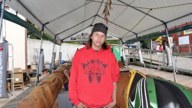 Eagleson Williams stands with the totem poles being carved by his father Rick as a memorial to the late John T. Williams