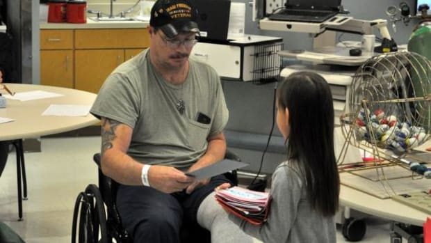 Military veteran Thomas Lynch receives a handmade Valentine's Day card from Cherokee Immersion Charter School kindergarten student Dayci Starr.