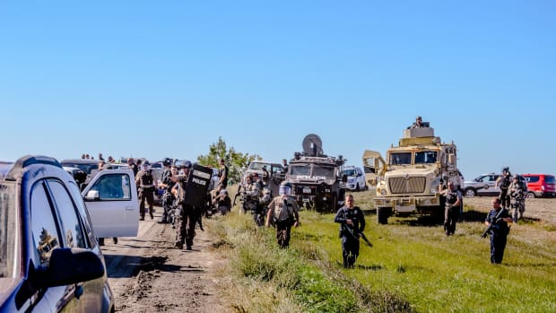 Police raise weapons and approach unarmed water protectors at a peaceful action on September 28, 2016