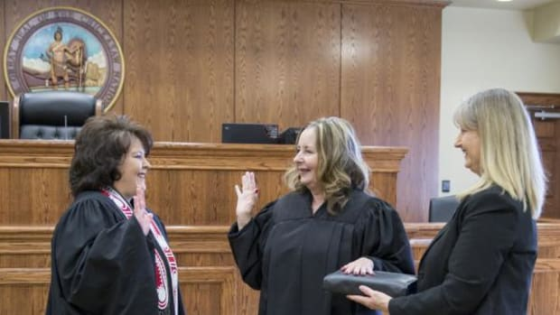 Chickasaw Nation Supreme Court Chief Justice Cheri Bellefeuille-Gordon, left, administers the oath of office to Sherry Abbott Todd as Special Judge of the District Court of the Chickasaw Nation. Todd was appointed to an additional 3-year term by justices of the Chickasaw Nation Supreme Court. Holding the Holy Bible is Todd's sister, Darla Abbott Porter.