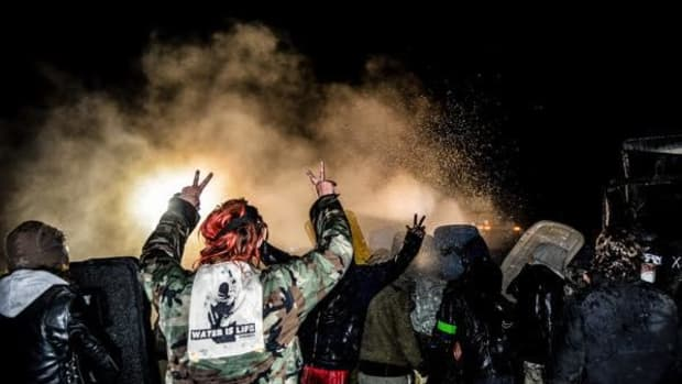Unarmed water protectors getting sprayed with water hoses, raising their hands in peace.
